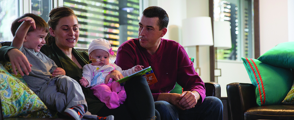 Mother and father on couch holding young son and baby daughter reading a book