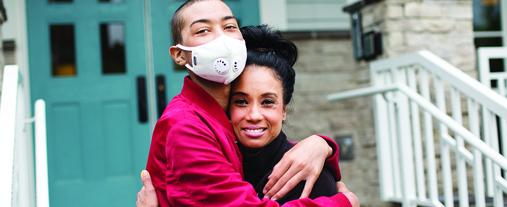 Mother hugging older son who is wearing a surgical mask
