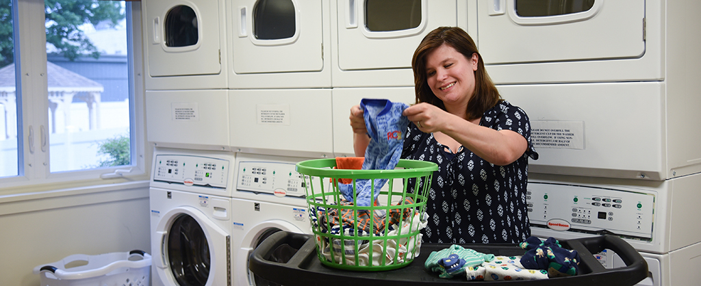 A mother folding her sons clothes in the RMHD laundry room.