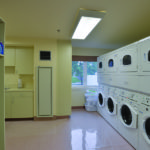 Bright and roomy laundry room with washers and dryers