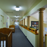 Hallway lined with donated cribs leading to guest rooms