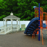 small gazebo with relaxing natural water fountain in view of playground slide