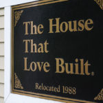 "A plaque located outside of the RMHD house, ""The House That Love Built""."