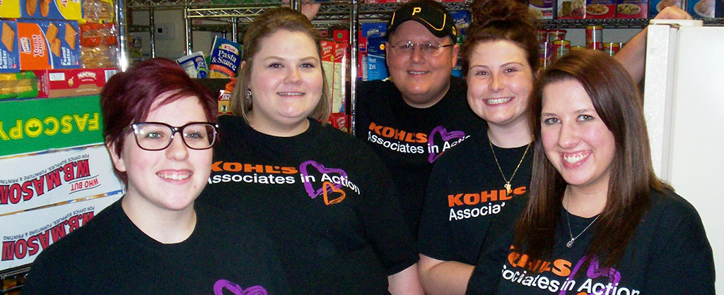 Volunteers smiling while standing in the stocked pantry closet.
