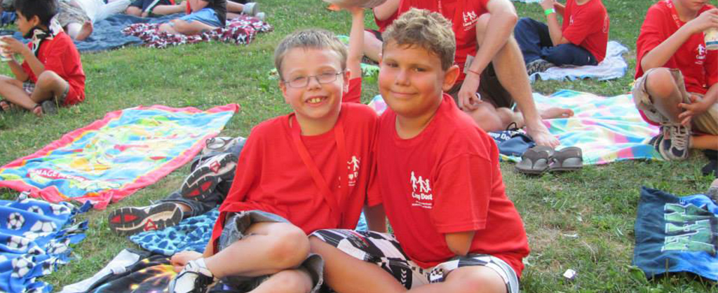 Two boys in red shirts smiling and sitting on a blanket at a Camp Dost event.
