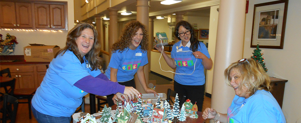 Volunteers smiling and excitedly working on a small Christmas display for the House.