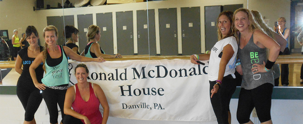 A group of girls in workout clothes smiling and excited to be fundraising for the Ronald McDonald House of Danville.