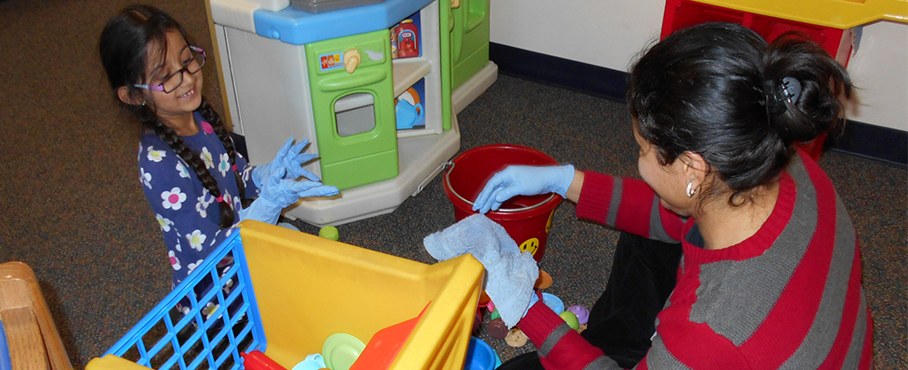A mother and daughter cleaning toys in the playroom.