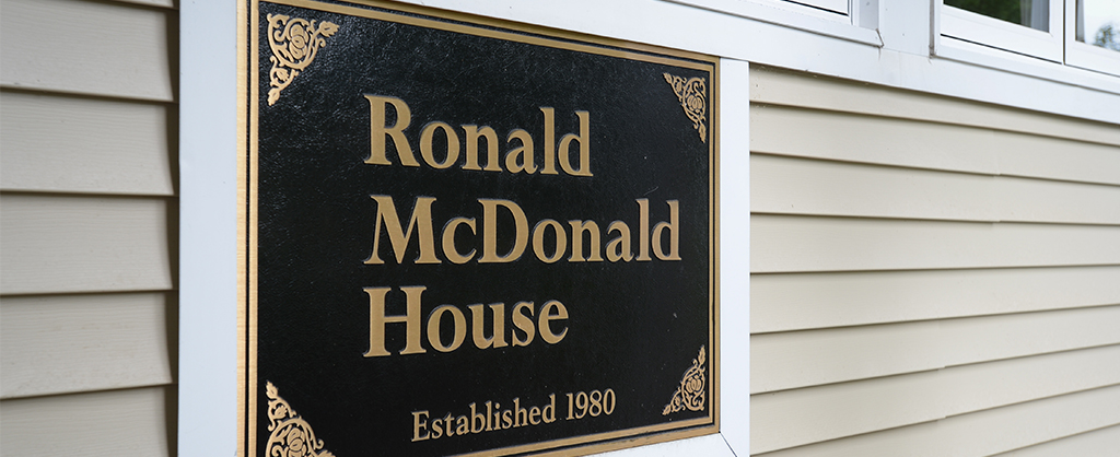 "A plaque outside of the house stating, ""Ronald McDonald House, Established 1980""."