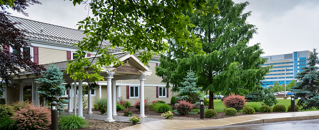 A view of the front exterior of the Ronald McDonald House of Danville with beautiful plants and Geisinger in the background.